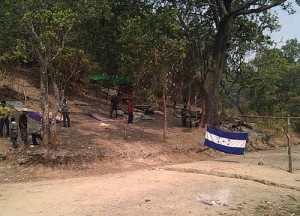 The Rio Blanco road block - a trench and a Honduran flag stretch across the road, and the communities are maintaining a constant presence in the trees to the side of the road